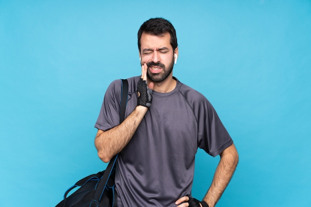 歯痛で孤立した青い背景上のひげを持つ若いスポーツ男 Premium写真