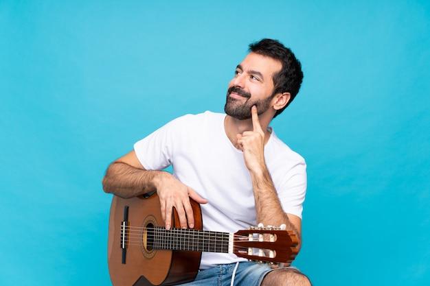 見上げながらアイデアを考えて分離青上のギターを持つ若い男 Premium写真