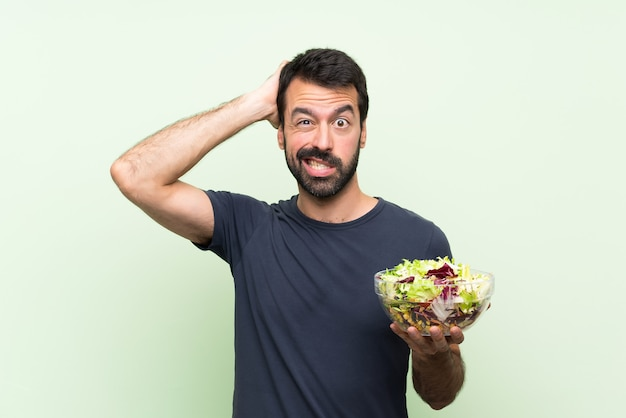 Молодой красавец с салатом на изолированной зеленой стене расстроен и берет руки на голову Premium Фотографии