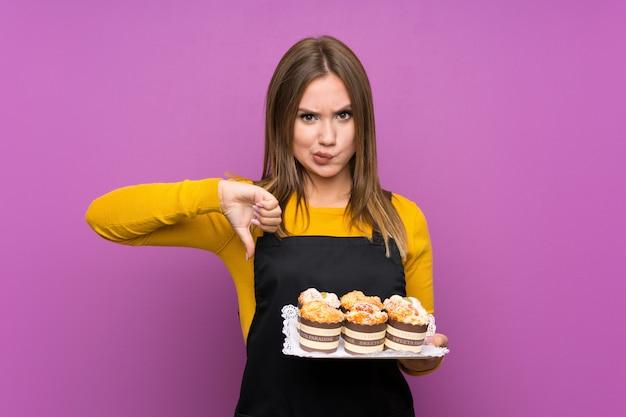 多くの異なるミニケーキを保持しているティーンエイジャーの女の子がサインをダウン親指を示す分離された紫 Premium写真