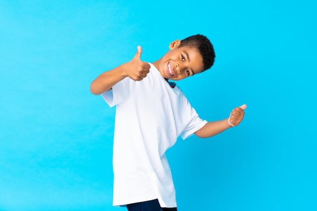 何か良いことが起こったので、親指で孤立した青い上のアフリカ系アメリカ人の少年 Premium写真