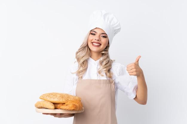 Девушка подростка в форме шеф-повара. женский пекарь держит стол с несколькими хлебов над изолированной белой, давая пальцы вверх жест Premium Фотографии