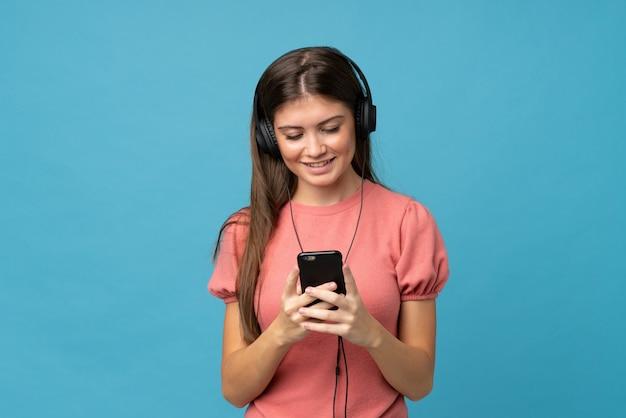 Молодая женщина над изолированным голубым используя чернь с наушниками Premium Фотографии