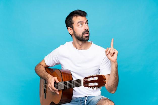 指を上向きのアイデアを考えて分離上のギターを持つ若い男 Premium写真