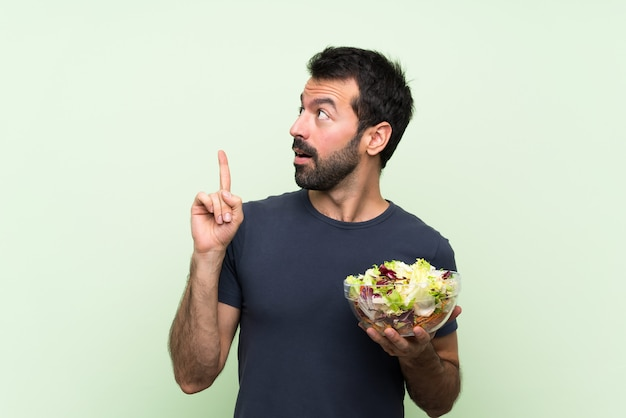 指を上向きのアイデアを考えて孤立した緑の壁の上のサラダと若いハンサムな男 Premium写真