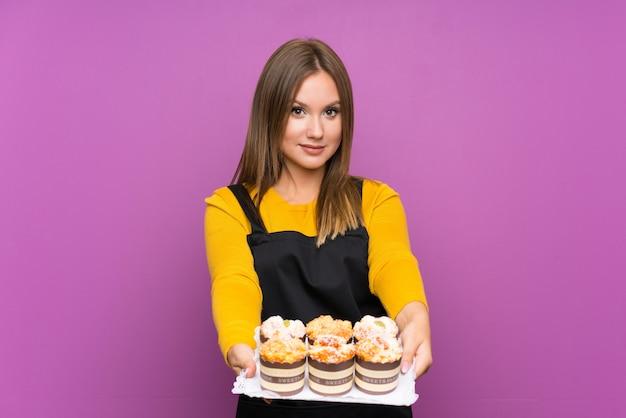 Девушка-подросток держит много различных мини-пирожных над изолированной Premium Фотографии