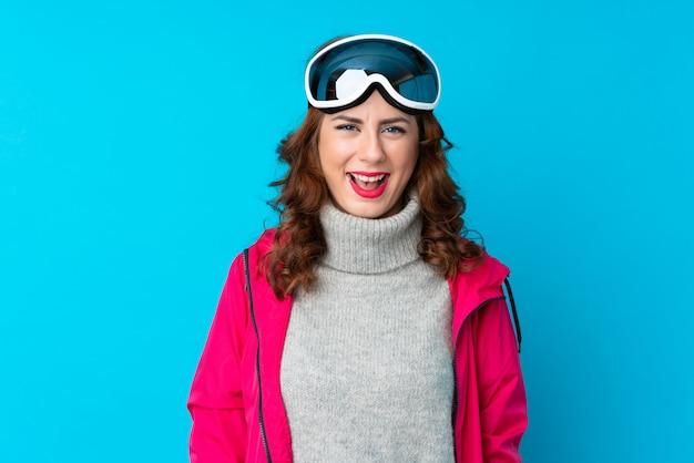 驚きの表情で孤立した青い壁の上のスノーボードメガネのスキーヤー女性 Premium写真