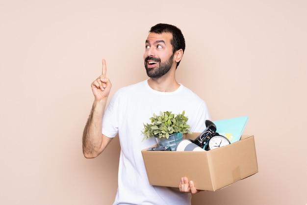 箱を押しながら指を持ち上げながら解決策を実現しようとする孤立した壁を越えて新しい家に移動する男 Premium写真