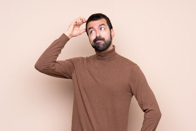 頭を掻きながら疑問を持つ孤立した壁の上の男 Premium写真