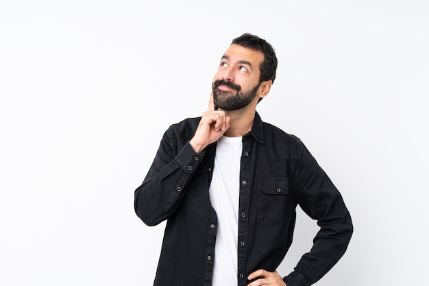 見上げながらアイデアを考えてひげを持つ若者 Premium写真