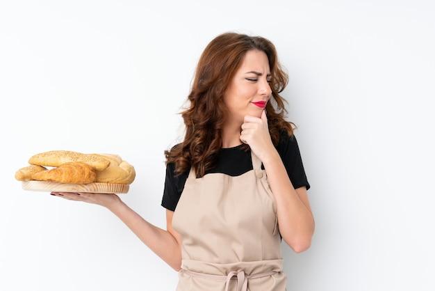 シェフの制服を着た女性。アイデアを考えて、側を見ていくつかのパンとテーブルを保持している女性のパン屋 Premium写真