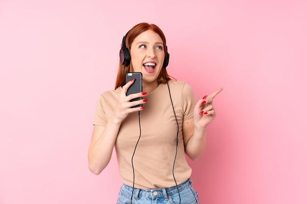 Молодая рыжая женщина на розовом фоне, используя мобильный телефон с наушниками и поет Premium Фотографии