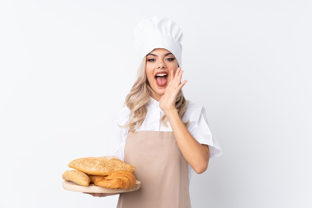 シェフの制服を着たティーンエイジャーの女の子。口を大きく開けて叫んで孤立した白い背景上にいくつかのパンとテーブルを保持している女性のパン屋 Premium写真