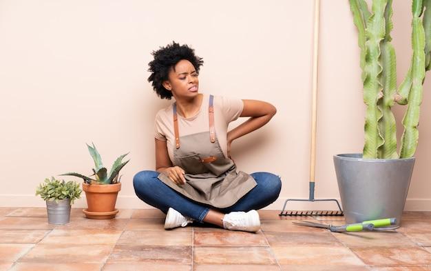 Садовник женщина сидит на полу вокруг растений Premium Фотографии