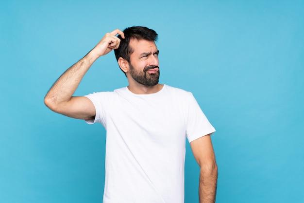 頭をかきながら疑問を持つひげを持つ若者 Premium写真