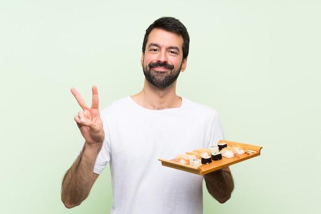 Молодой красавец с суши, показывая знак победы обеими руками Premium Фотографии