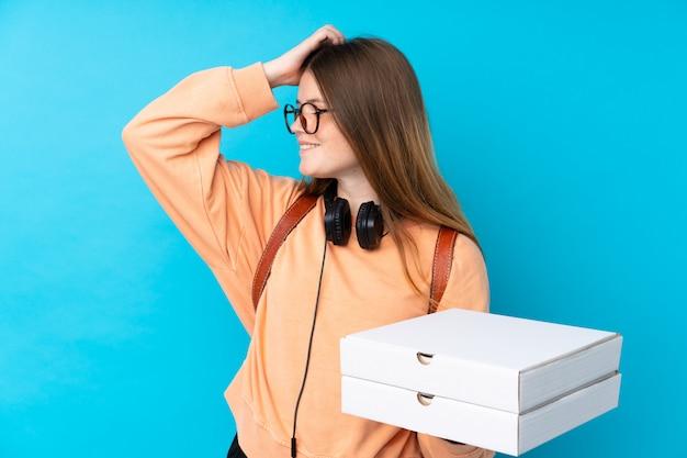 青い背景上にピザの箱を置く少女 Premium写真