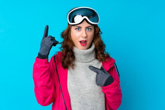 驚きの表情でスノーボードメガネのスキーヤー女性 Premium写真