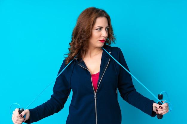 縄跳びを持つ若いスポーツ女性 Premium写真