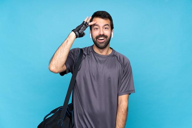 孤立した青い壁の上のひげを持つ若いスポーツ男はちょうど何かを実現し、解決策を意図しています Premium写真