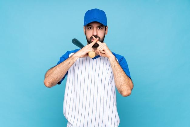 沈黙のジェスチャーの兆しを見せ分離の青い壁で野球をしている若い男 Premium写真