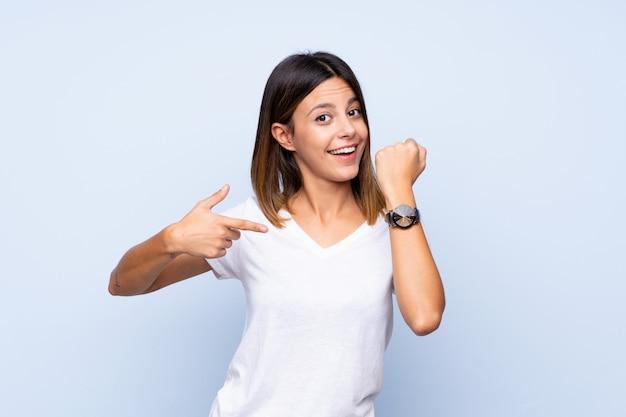 手時計を示す分離の青い壁の上の若い女性 Premium写真