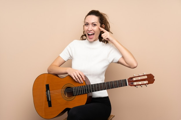 解決策を実現しようとしている孤立した壁の上のギターを持つ若い女性 Premium写真