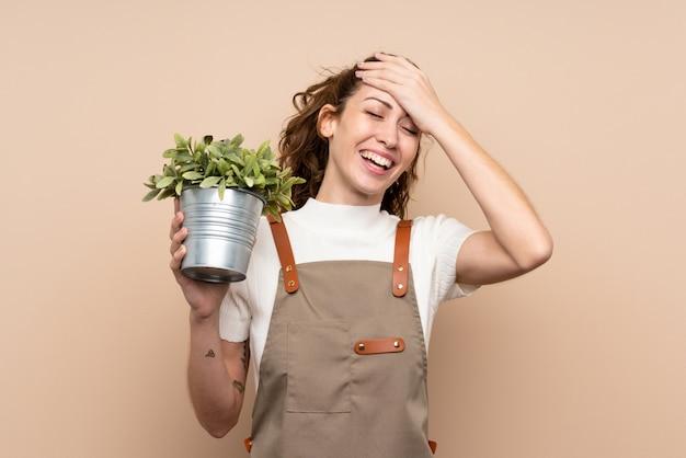 植物を保持している庭師の女性が何かを実現し、解決策を意図している Premium写真