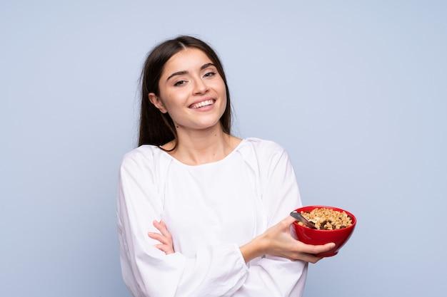穀物のボウルを保持している孤立した青い壁の上の若い女性 Premium写真