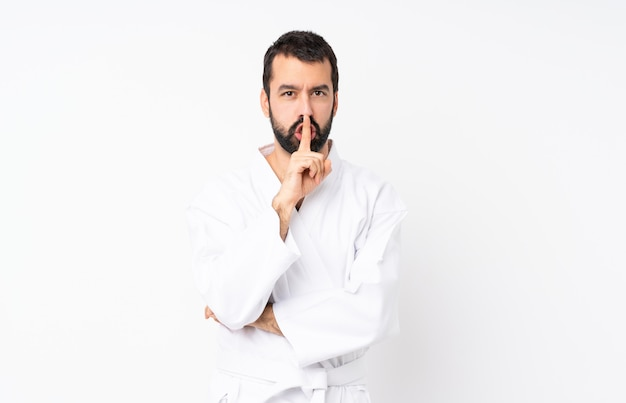 口に指を入れて沈黙ジェスチャーの兆候を示す分離の白い壁に空手をやっている若い男 Premium写真