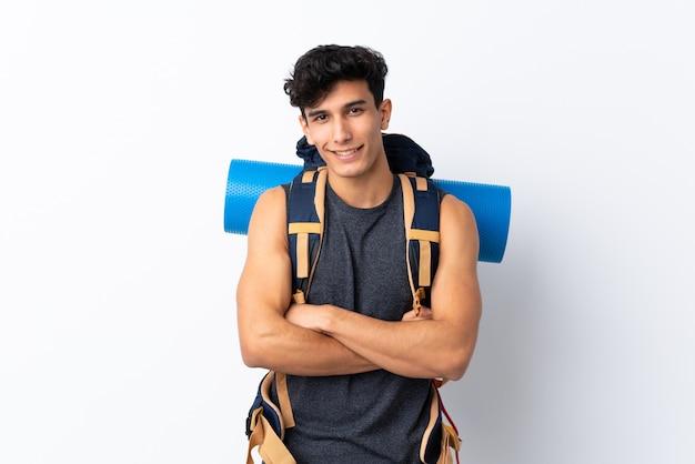 笑っている孤立した白い壁の上の若いアルゼンチンハイカー男 Premium写真