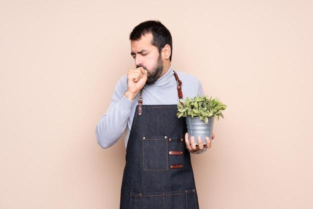 孤立した壁を越えて植物を保持している男は咳と気分が悪い Premium写真