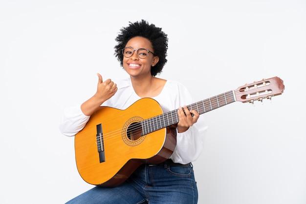 Женщина с гитарой на белой стене Premium Фотографии