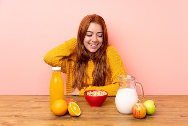 Рыжая девушка подросток завтракает в таблице смеется Premium Фотографии