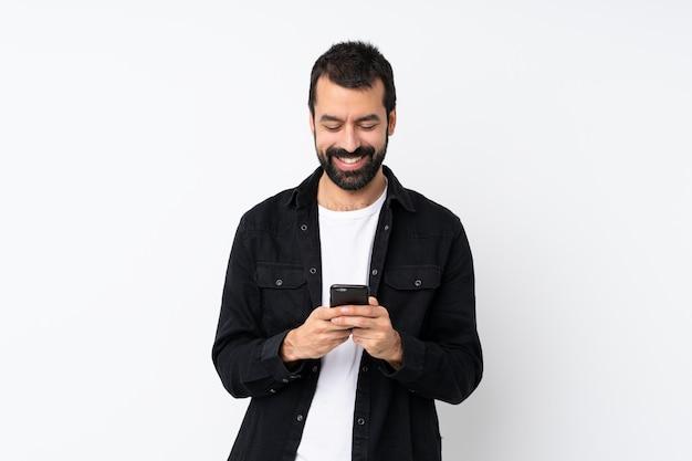 携帯電話でメッセージを送信する分離白でひげを持つ若者 Premium写真
