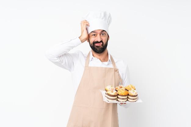 欲求不満の表現と理解していない分離白にマフィンケーキを置く若い男 Premium写真