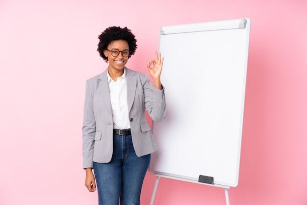 ピンクの壁の上のアフロアメリカンビジネス女性 Premium写真