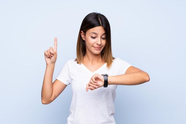 Молодая женщина над изолированным голубым смотрящ на вахте руки Premium Фотографии