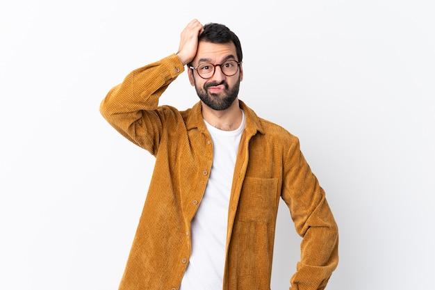 欲求不満の表現と理解していない孤立した白い壁にコーデュロイのジャケットを着てひげを持つ白人のハンサムな男 Premium写真