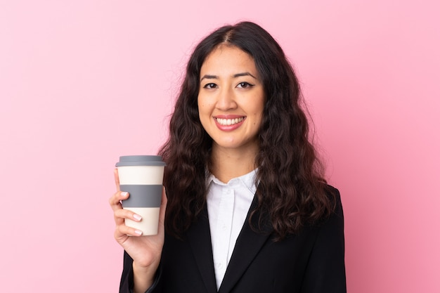 孤立したピンクの壁を奪うためにコーヒーを保持している混血ビジネス女性 Premium写真