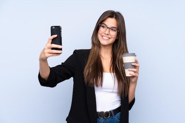 奪うためにコーヒーを保持している若いビジネス女性 Premium写真