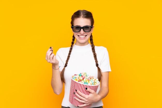孤立した壁の上のポップコーンを持つ若い女性 Premium写真