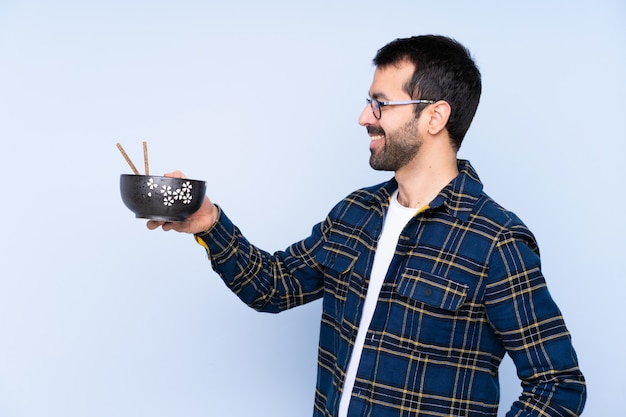 孤立した壁に麺を食べる男 Premium写真
