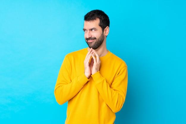 孤立した青い壁の上のひげを持つ男 Premium写真