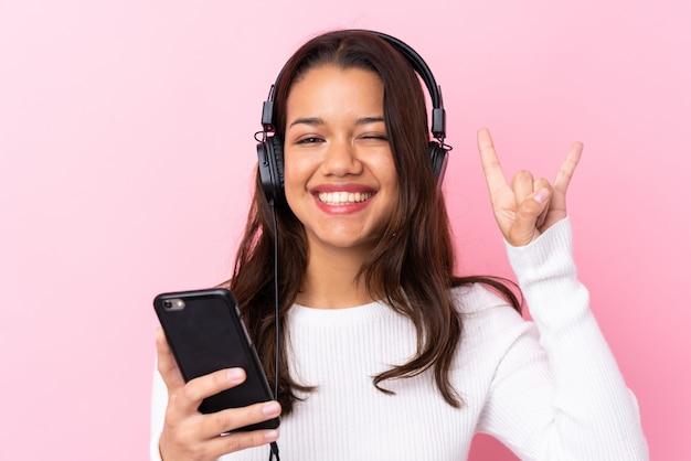 Молодая женщина с наушниками над изолированной розовой стеной Premium Фотографии