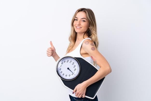 親指で計量機を保持している孤立した白い壁の上の若い女性 Premium写真