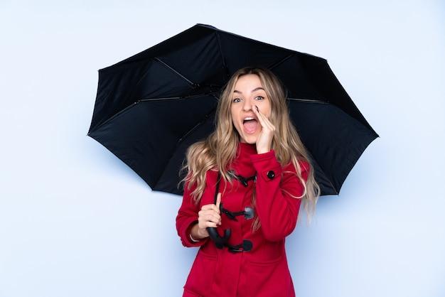 冬のコートと口を大きく開いて叫んで傘を保持している若い女性 Premium写真