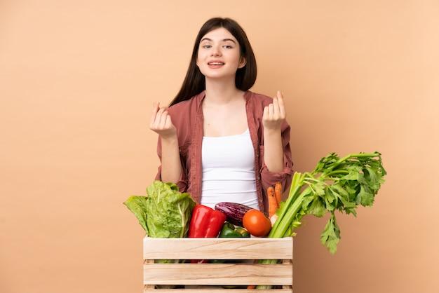 お金のジェスチャーを作るボックスで採れたての野菜を持つ若い農家の少女 Premium写真