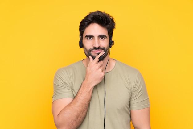 Телемаркетер человек, работающий с гарнитурой над желтой стене смеется Premium Фотографии