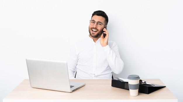 Молодой предприниматель на рабочем месте, ведение разговора с мобильным телефоном Premium Фотографии
